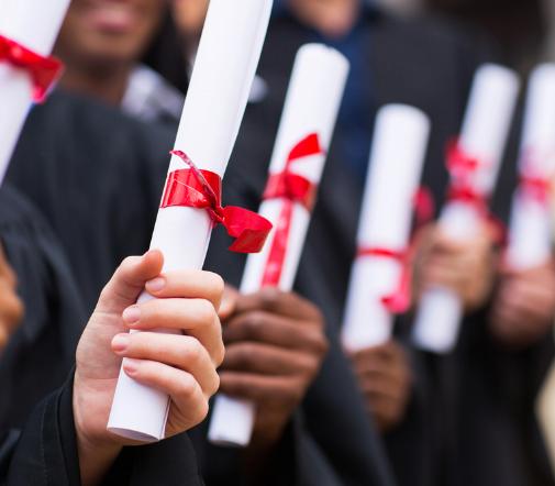 A photo of graduates holding diplomas